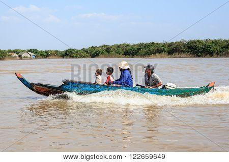 Tonle sap lake near Siem Reap Cambodia January 14 2014: Family on boat near floating village on tonle sap lake near siem reap cambodia.