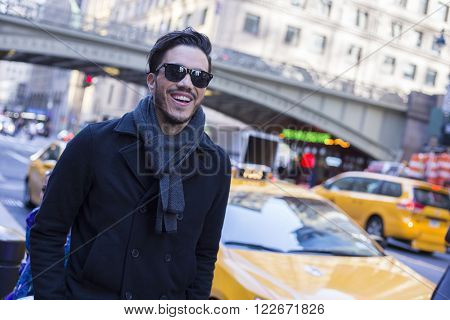 Young man with a black coat and sunglasses wandering in New York in a cold day