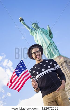 Tourist in New York visiting the Statue of Liberty with an american flag