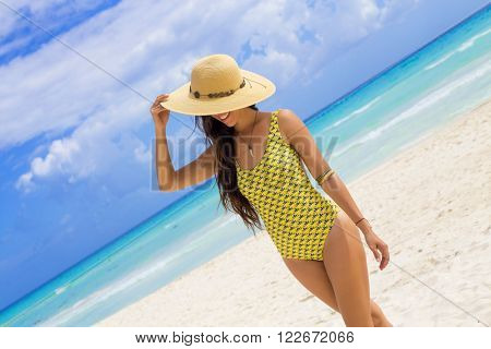 Woman with a yellow swimsuit and a hat in the Caribbean