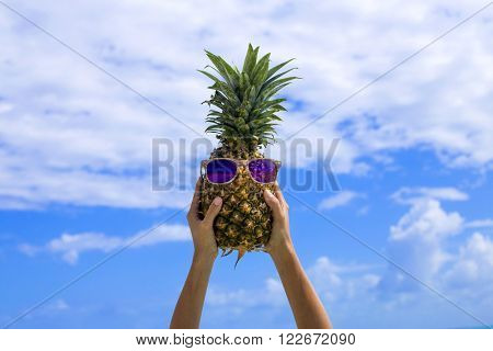 Woman hands holding a pineapple against a blue sky