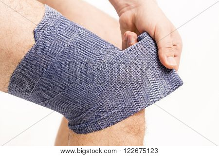 man putting  elastic bandage on knee pain health France