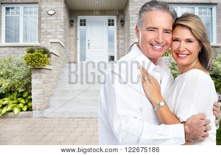 Happy senior couple near new house.
