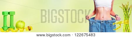 Slimming woman wearing big pants over green background.