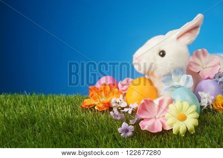 Festive Easter background with rabbit, flowers, and colorful eggs