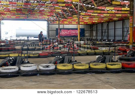 O'CONNOR,WA,AUSTRALIA-MARCH 5,2016: Indoor Kart Hire racing with go karts and colourful tire boundaries with people in O'Connor, Western Australia.