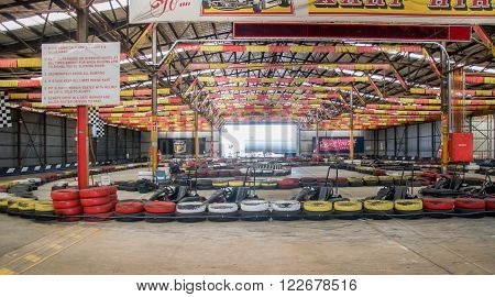 O'CONNOR,WA,AUSTRALIA-MARCH 5,2016: Indoor Kart Hire location with go karts, colourful tires and flag display with people in O'Connor, Western Australia.
