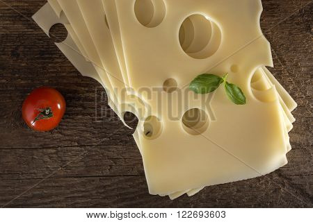 Slices of Emmental cheese on a wooden background