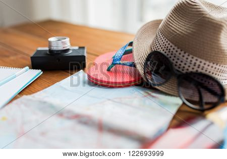summer vacation, tourism and objects concept - close up of travel map, flip-flops, hat and camera on wooden table at home