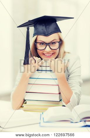 picture of happy student in graduation cap with stack of books