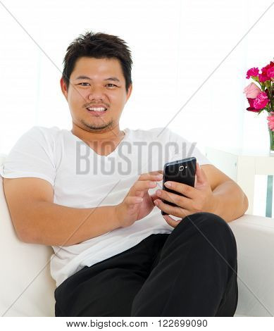 Asian man sitting on sofa and using handphone