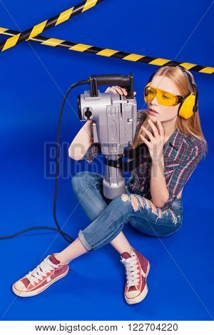 Builder Girl On A Blue Background With A Professional Building Tool In A Protective Helmet