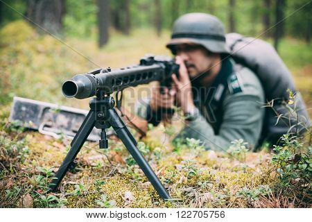 Hidden unidentified re-enactor dressed as german wehrmacht soldier aiming a machine gun at enemy from trench in forest ** Note: Shallow depth of field