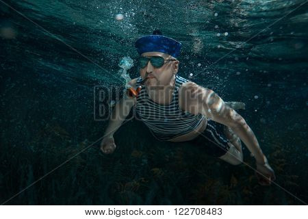 Seaman swims under water and smokes a pipe.