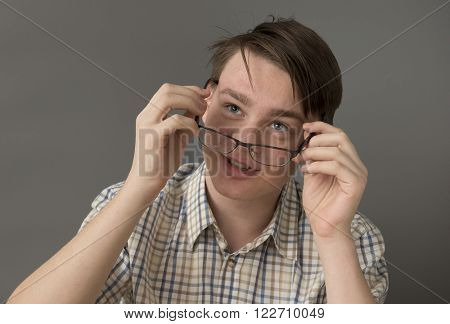 Portrait of a teenage boy looking over his glasses