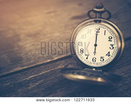 Retro pocket watch with antique number is showing 6 o'clock on wooden background. Vintage style and filtered process.