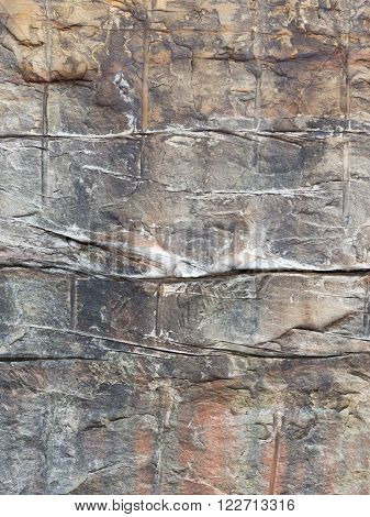 Old wall from a decorative brown and gray stone with a rough cleaved surface vertically