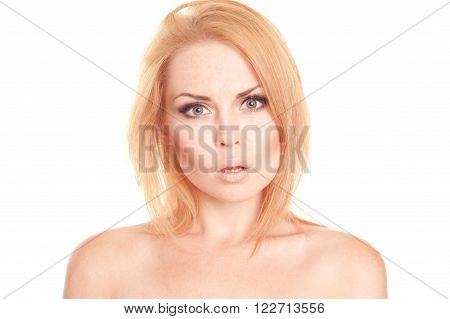 Young blonde girl 20-25 years old looks surprised over white. Closeup portrait of beautiful woman posing in studio. Isolated.