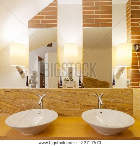 Two washbasins in elegant wood and marble bathroom