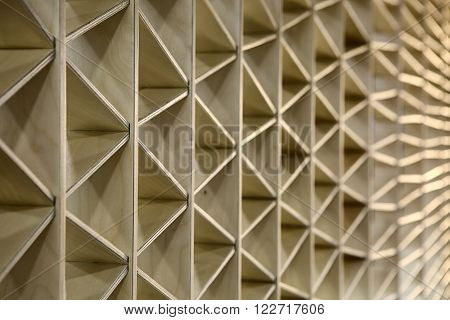 Ornamental light wooden partition. The ornament consists of triangles. Horizontal.