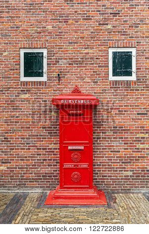Old red postbox in front of brick wall in Zaanse Schans, Netherlands.