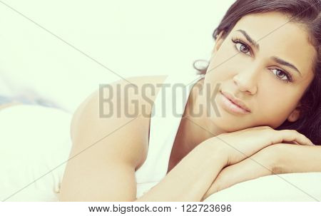 Instagram style portrait of a beautiful young Latina Hispanic young woman or girl looking thoughtful resting on her hands
