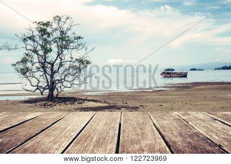 Wooden terrace with defocus the beach tree and old wooden ship background, vintage tone