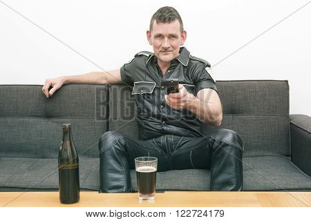 man wearing black fetish leather clothes and sitting on couch watching tv