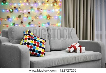 Grey couch with pillow and gifts on Christmas lights background