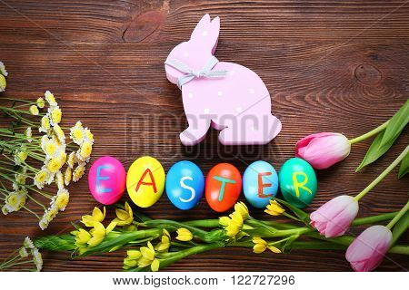 Easter eggs with spring flowers and rabbit on wooden background