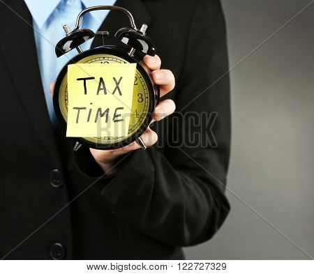 Woman in black suit holding alarm with tax time inscription on grey background