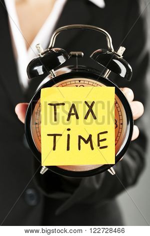 Woman in black suit holding alarm with tax time inscription, close up