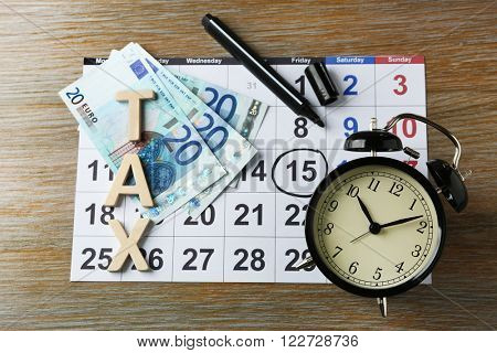 Tax time and alarm clock with euro, marker and calendar