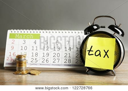 Tax time on alarm clock with coins and calendar