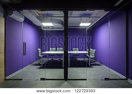 Room for meetings with violet walls. Front wall is glass with glass doors. There are two gray tables with several chairs around them. On the floor there are gray tiles. At the top there are communications and lamps.