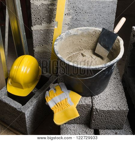 Tools for bricklayer bucket with a solution and a trowel, close-up