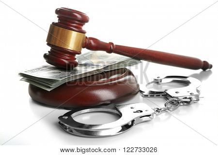 Law gavel with dollars and handcuffs isolated on white