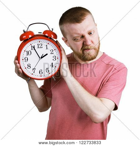 Bearded man listening to the ticking of alarm clock