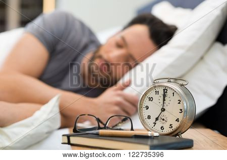 Young man sleeping in his bedroom. Man sleeping with an alarm clock in foreground. A calm man in his bed before waking up in his room. Close up of alarm clock on bedside table.