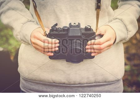 Woman hands holding retro photo camera walking outdoor Lifestyle hipster Travel concept retro colors