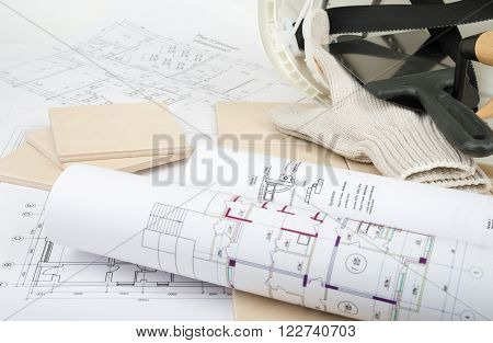 Set of tiles and tile wall with pallet-knife and helmet. Building concept
