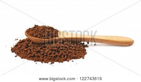 Pile of instant coffee grains with the wooden spoon over it, composition isolated over the white background
