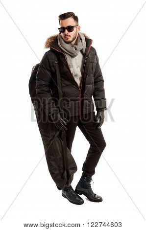Business man ready to go to ski wearing winter clothes and a big long bag
