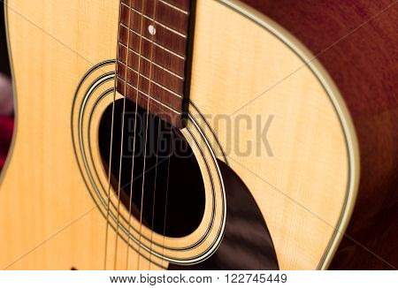 yellow six-string acoustic guitar with black elements close-up. isolated.