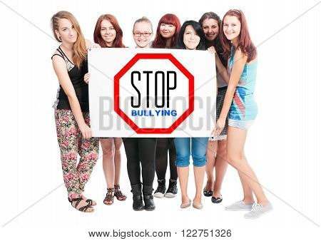Stop bullying concept written on cardboard held by a bunch of young girl on white background poster