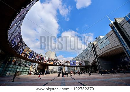 BRUSSELS BELGIUM - MARCH 16: Wide angle shot with people walking by European Parliament's Leopold Square on March 16 2016 in Brussels.