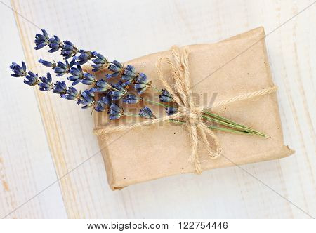 Handmade simple cute gift wrapping. Gift box in parchment paper and dried lavender twig decor.