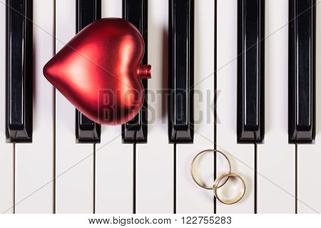 Detail of piano keyboard ,red heart and wedding rings