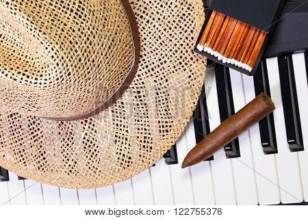 Detail of piano keyboardstraw hat and luxury cigar