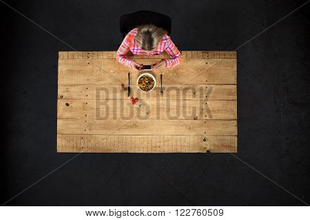 Top view creative photo of girl sitting at wooden vintage table. Girl with plate full of delicious meal. Girl using mobile phone